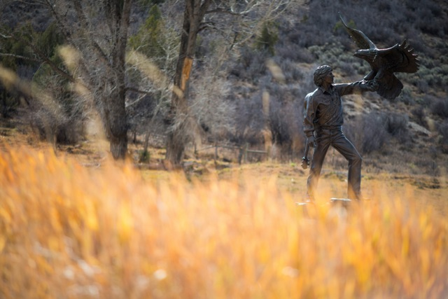 A statue of John Denver stands tall behind autumn grass in the Windstar meadow.