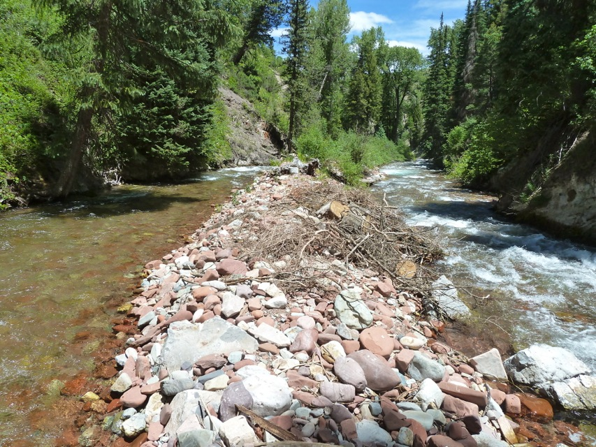 Looking down Maroon Creek, the water diverted for the Stapleton Bros. ditch is sent to the left of a rock island, while Maroon Creek flows to the right. The structure is in a narrow gorge below Iselin Field and just upstream of the base of Tiehack.