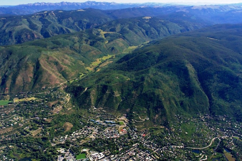 An aerial view showing urban Aspen, the dark forested slopes of Smuggler Mountain and the lush Hunter Creek valley.