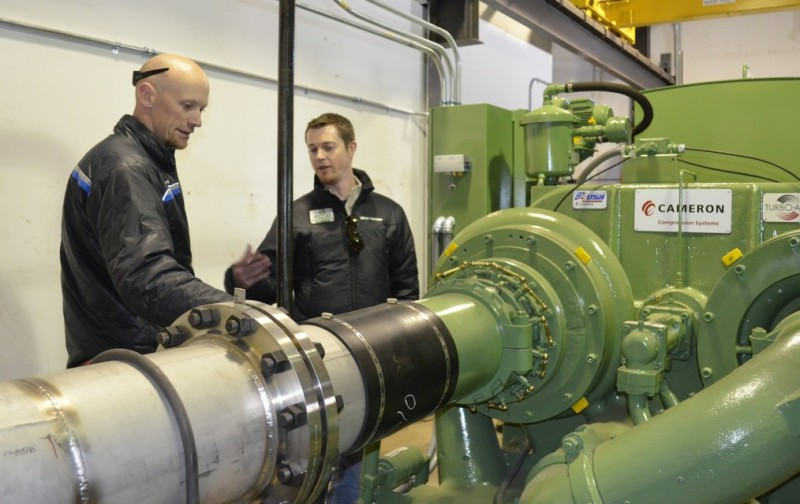 Luke Cartin (left) and Sean Conboy discuss the benefits of a new air compressor for the snowmaking system at Vail Mountain. The device uses half the electricity of eight old compressors it replaced, while producing 30 percent more compressed air.