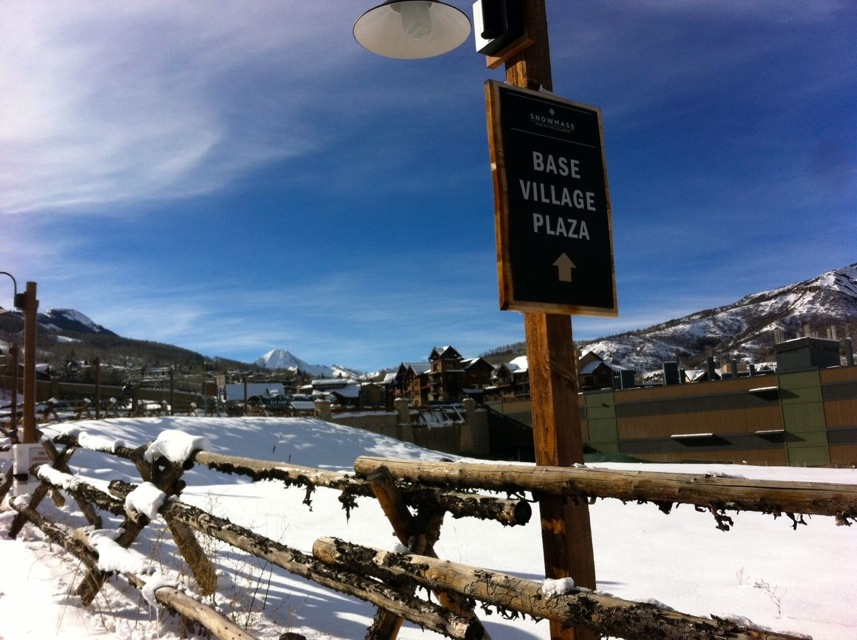 A sign for the Base Village plaza along Wood Road. In the background is the unfinished Building 8, originally designed to be a Little Nell Snowmass hotel.