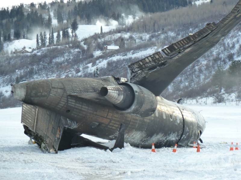 The wreckage of a private jet on the runway in Aspen, Colorado on Sunday, Jan. 5, 2014. In the background, snowmaking guns are making snow on Buttermilk Mtn for the X Games.