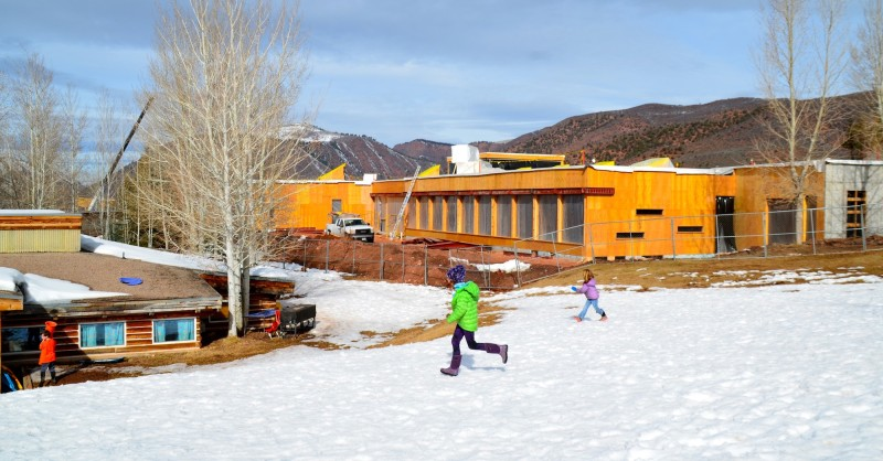 As a new main building rises on the right, children at the Aspen Community School return to classes in the aging log building at left.