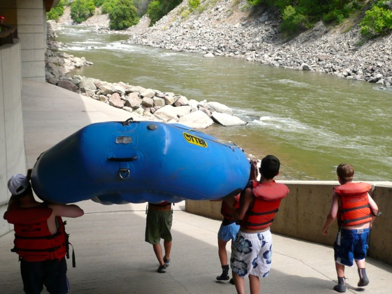 A group of paying customers help carry a boat down the Shoshone boat ramp as part of a commercial raft trip.