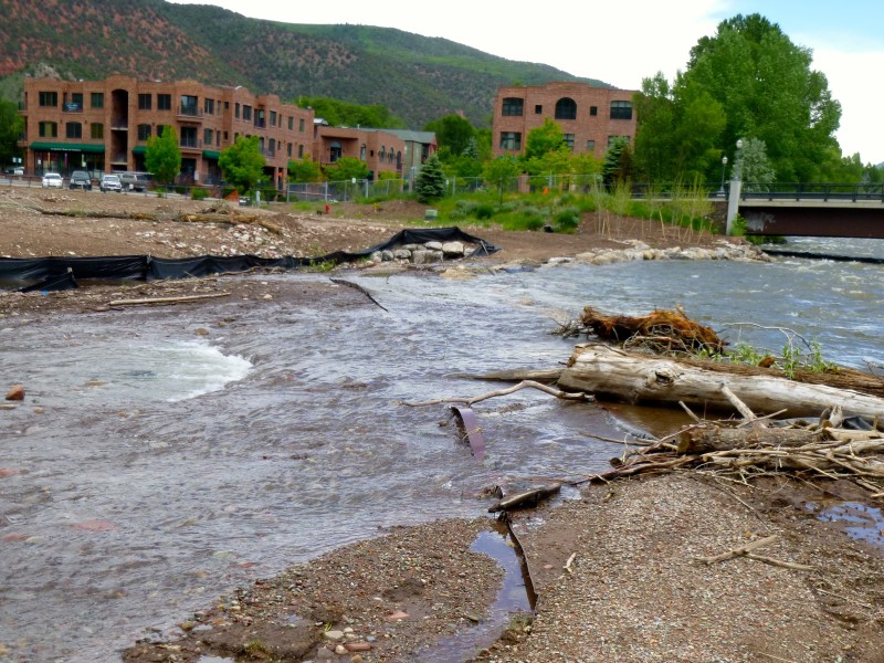 The Roaring Fork River, flowing over 3,000 cfs, has over topped new rock work installed in Basalt. The rock was designed to let the river flow over it, but the river has washed away topsoil and portions of a new gravel path.
