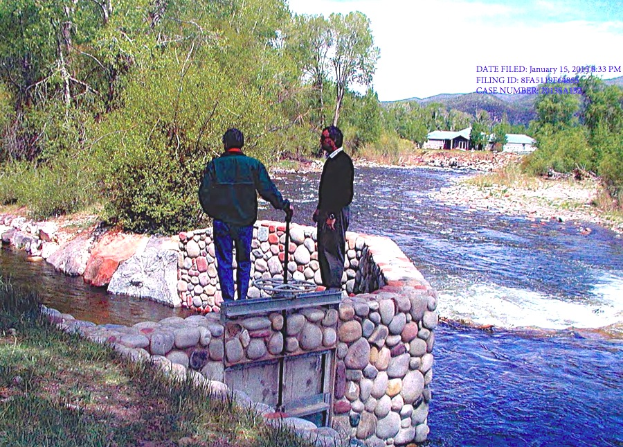 The Roaring River, looking downstream, with two men standing on an irrigation headgate, river left, at the Roaring Fork Club. The High Valley Farms facility is just upstream, river right, and not in the photo.