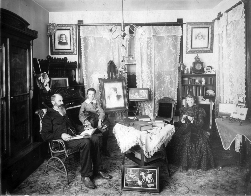 Judge B. F. Porter and family enjoy the Victorian Life in their Aspen residence. Decor includes an organ, lace curtains, book shelves, framed art, a birdcage and clock. Circa 1895.