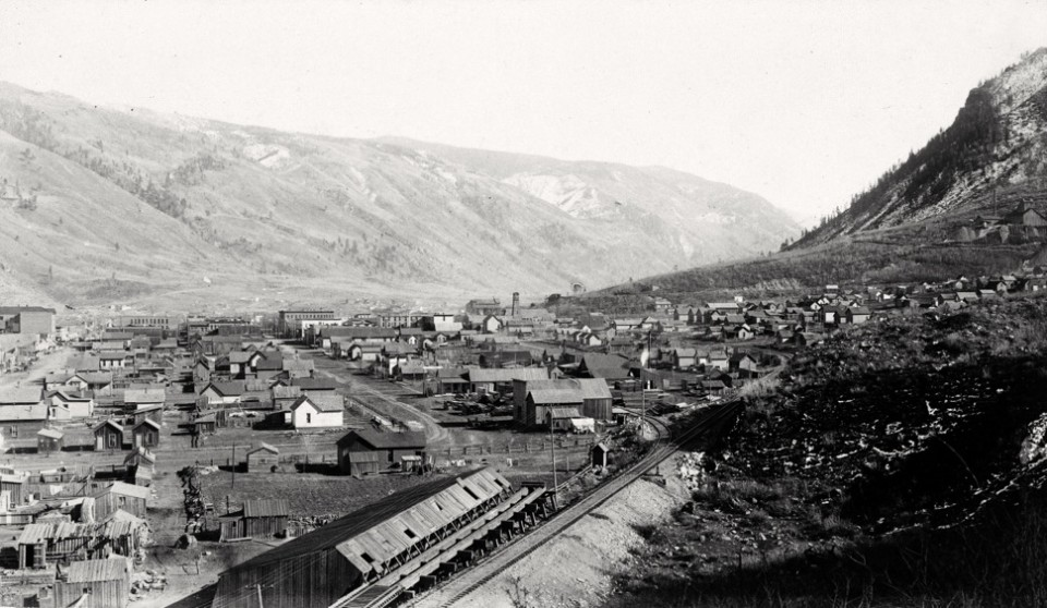 A view from Shadow Mountain shows the Colorado Midland Railroad track entering Aspen in 1892  or 1893. The Koch Lumber Company—now Koch Park—is in the middle of the photo. The Midland RR ore terminal is in the background, near  today's Little Nell hotel and the base of gondola plaza. The Public Tram towers are visible on the horizon of what is now the Little Nell ski trail.