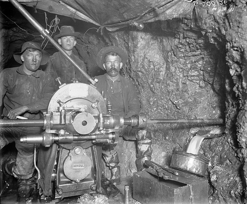 The inscrutable faces of three miners reflect the hard work of drilling for silver in the Smuggler Mine, circa 1890 to 1900.