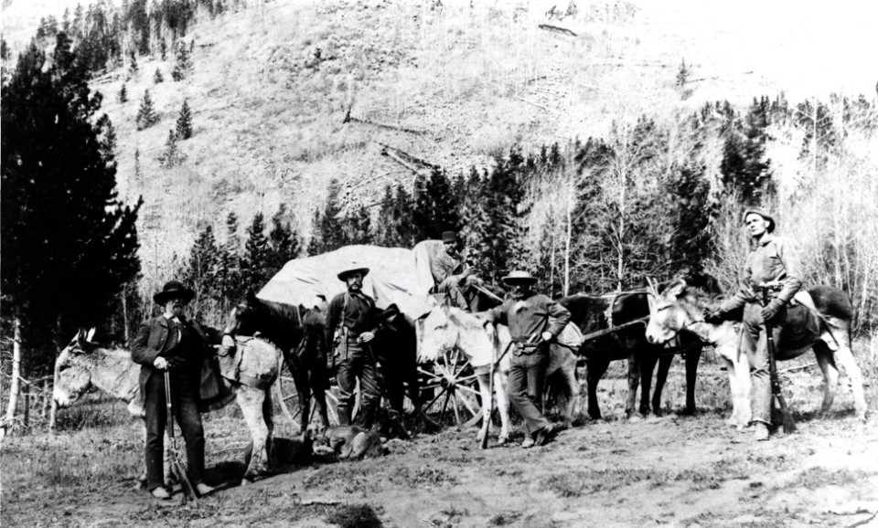 Men with rifles, a wagon, and burros in Tourtelotte Park circa 1890. What is today's Face of Bell, and possibly the Hanging Tree line,  appears to be the backdrop.