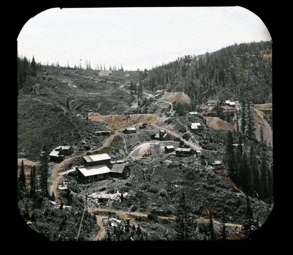 A colorized lantern slide of Tourtelotte, circa 1890-1893, shows mine buildings and homes. Three Aspen Public Tram towers are barely visible in the middle rising to the terminal at the bottom of today's Pumphouse ski run.