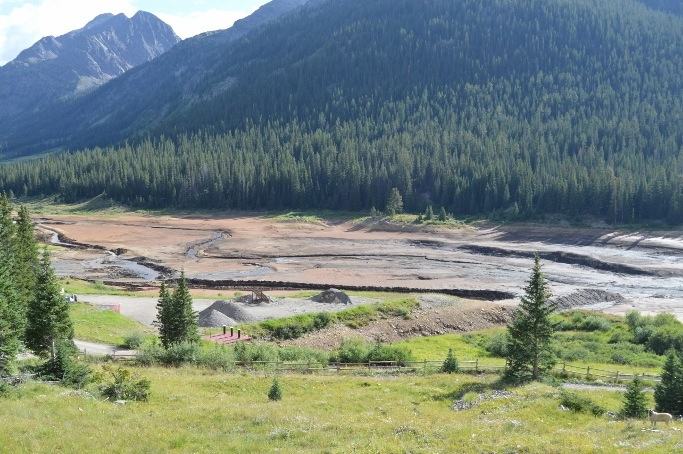 A view of the recently drained Grizzly Reservoir. Operators are now cutting a drainage channel to divert the flows of Grizzly and Lincoln creeks directly into a diversion tunnel so they can inspect the damaged outlet works on the dam.