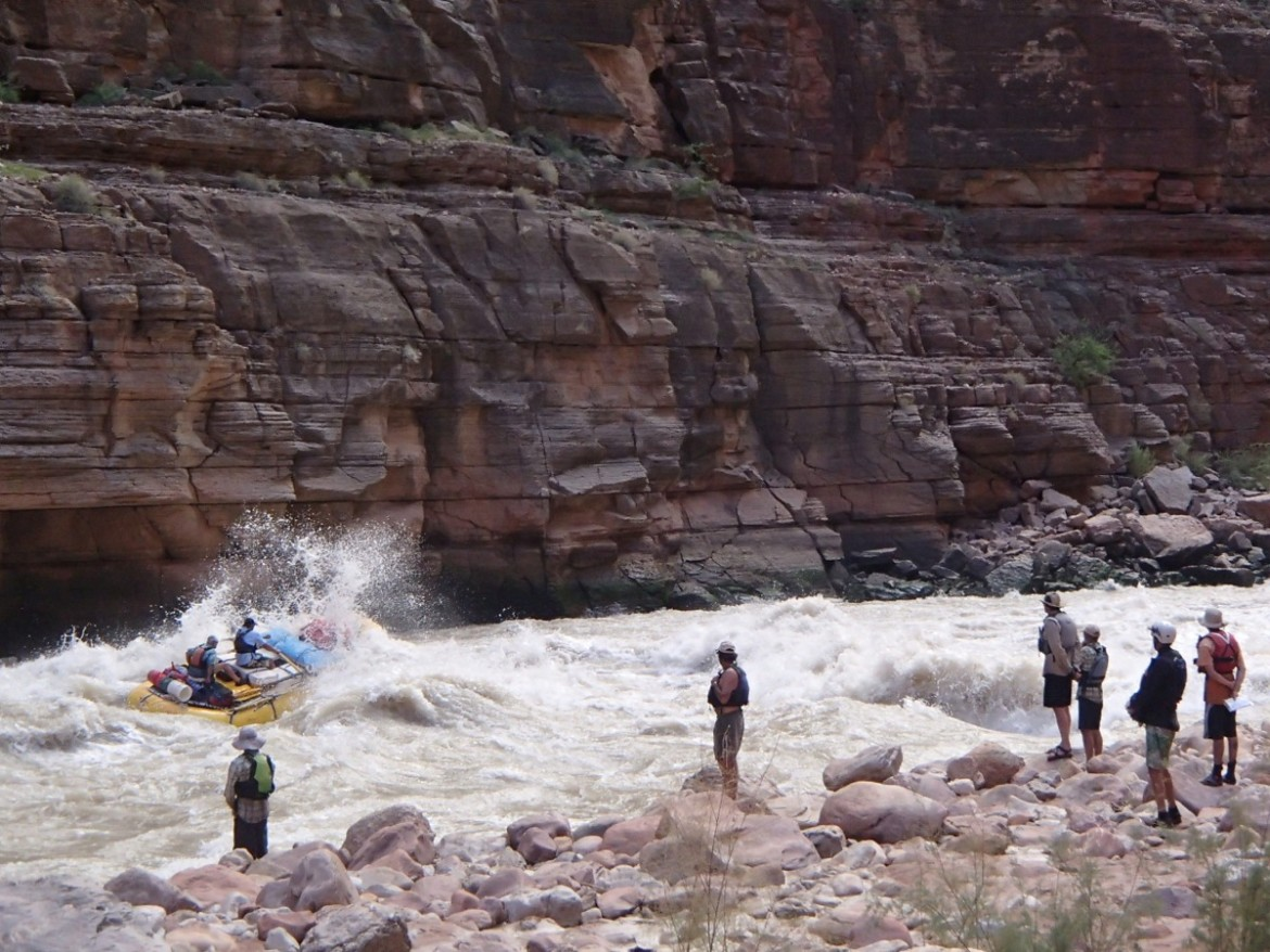 A group of boaters watch as a raft runs Upset Rapid on the Colorado River below Glen Canyon Dam.