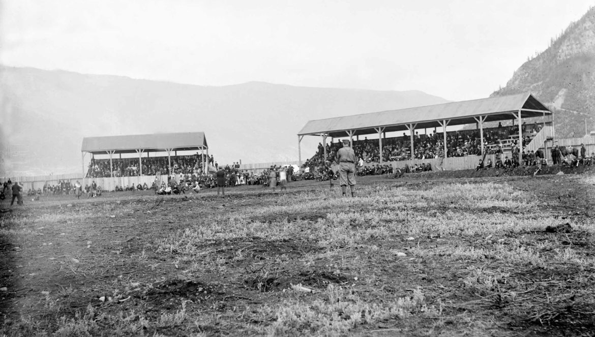 The stands are packed for a baseball game in Aspen's baseball stadium (one of two) located where today's Aspen golf course abuts the roundabout. Note the fence around the park and Shadow Mountain in the background, right.
