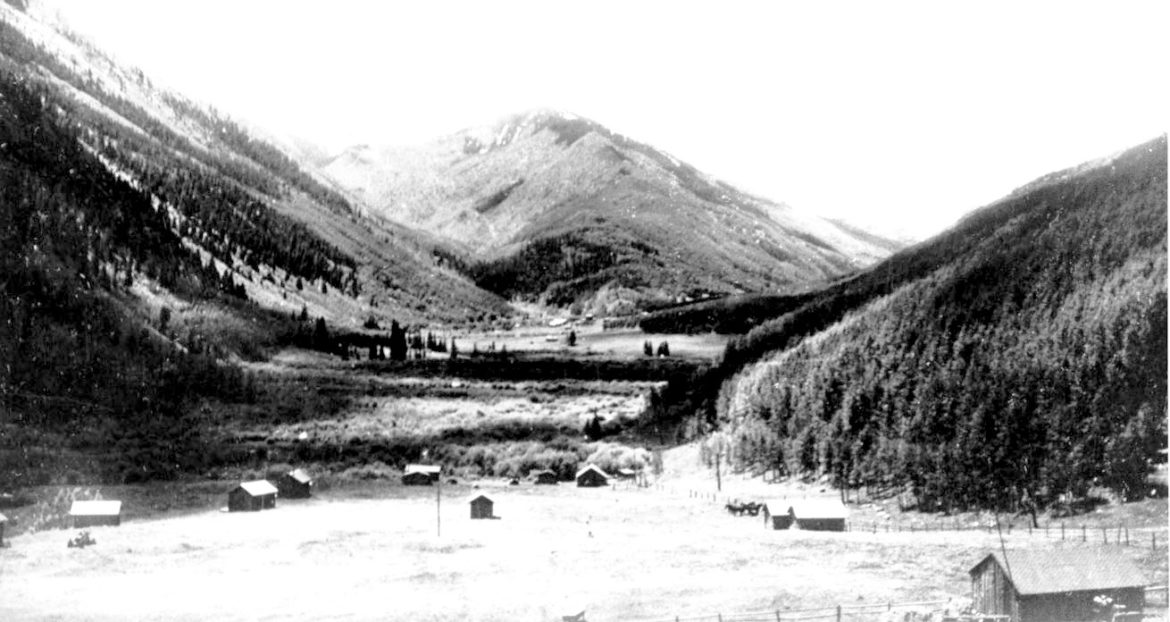 A view of the Castle Creek Valley and the location of the Elk Mountain lodge, looking toward Ashcroft, taken in 1965. A caption below the photo read: Vacation at Elk Mountain Lodge, where scenic beauty, good fishing, perfect climate, and hospitality abound. Ten miles of stream and three lakes. Eleven furnished cabins. Saddle horses, home cooked meals if desired.