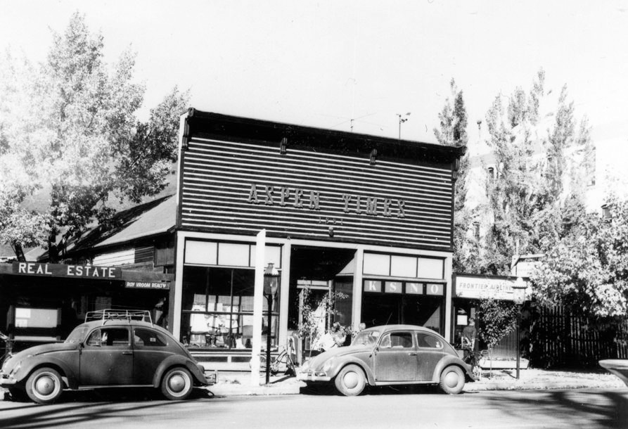 One b/w photograph of the Aspen Times building on Main Street, 1965. The business on the left is Roy Vroom Realty, and on the right is Frontier Airlines. There is also a sign in the window of the Aspen Times building for Aspen radio station KSNO, which had their studio there (publisher Bil Dunaway was president of the radio corporation).