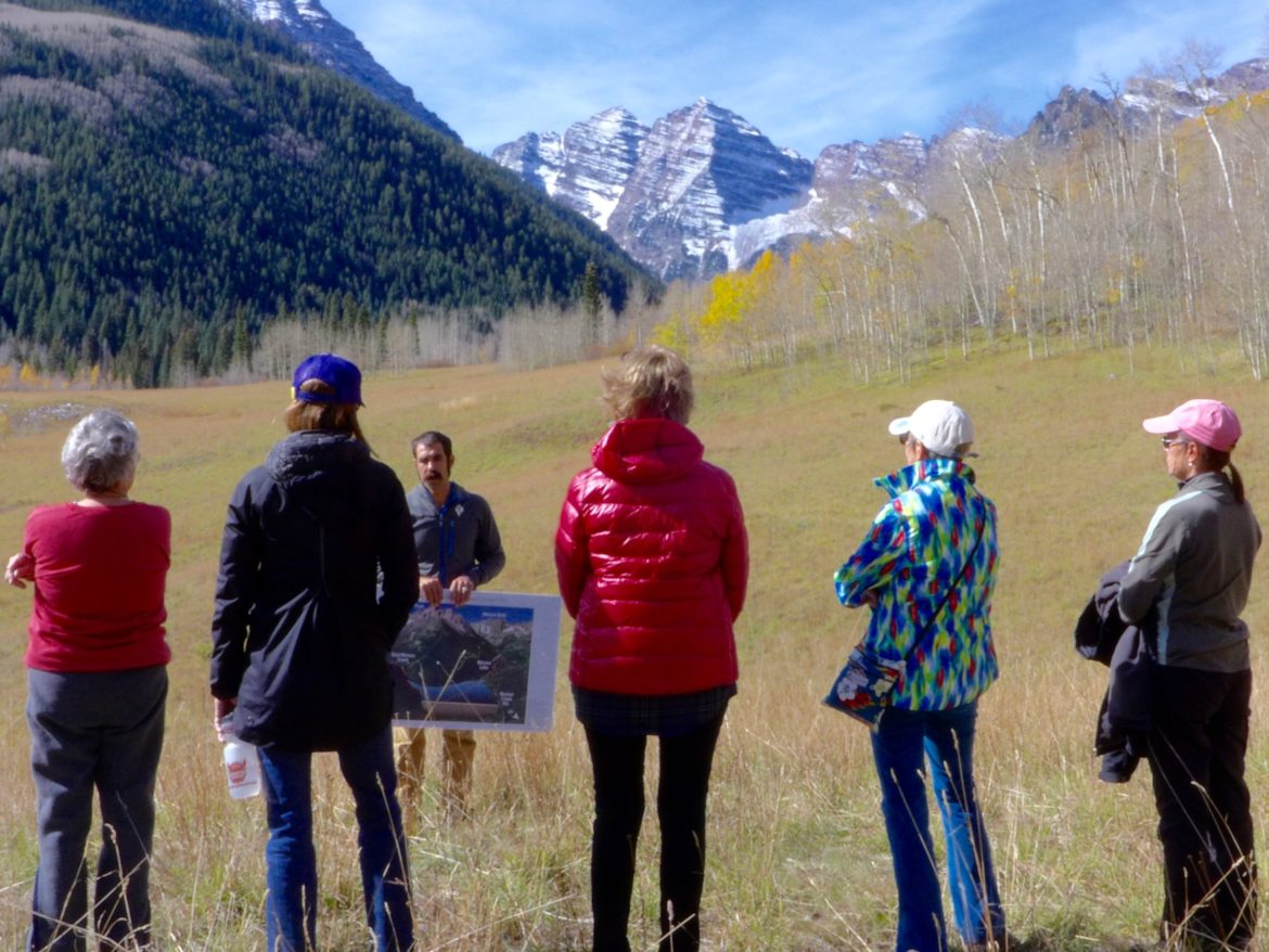A group of local residents listen as Will Roush, the conservation director for Wilderness Workshop of Carbondale, describes the location, and potential impacts of, the city of Aspen's proposed Maroon Creek dam and reservoir. The 155-foot-tall dam would be built across Maroon Creek and across the wedding meadow, just behind where Roush is standing.