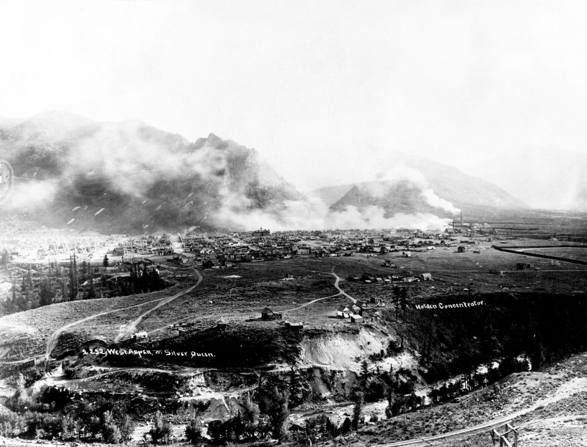 Viewed from Red Mountain, the Silver Queen lies in Aspen Mountain with her face looking to the sky from Shadow Mountain. Smoke from the chimneys of the Holden Lixiviation plant that is processing silver ore from her veins surrounds her in 1892.