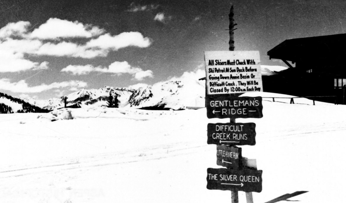 "A sign at the top of Aspen Mountain in 1950 shows the Silver Queen trail starting atop Aspen Mountain. The trail went down Buckhorn, across Midway Road, down International, and down what is today's steep Silver Queen run on lower Aspen Mountain The sign says '""ll skiers must check with ski patrol at Sundeck before going down Annie Basin or Difficult Creek. They will be closed by 12:00 each day."" The first version of the Sundeck, known as the Octagon, is partially visible behind the sign."