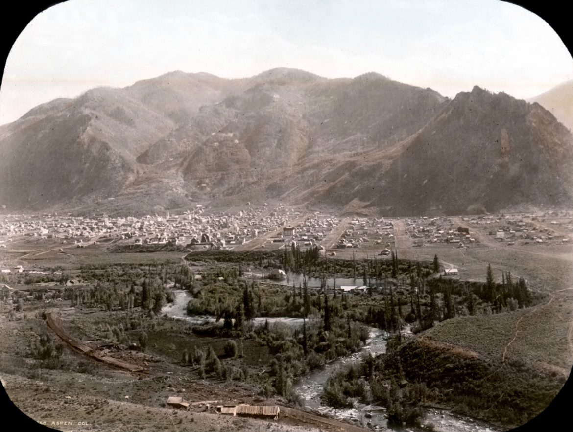 A colorized lantern slide shows a panoramic view of Aspen from Red Mountain. An outline of the Silver Queen (or the Ute Chief) can be clearly seen in West Aspen Mountain, now known as Shadow Mountain. The picture was likely taken in late summer of 1887.