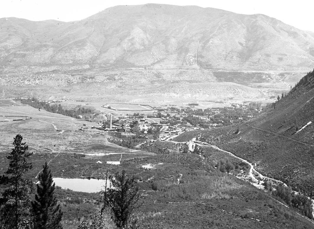 This 1900 view of Aspen, from the lower Castle Creek valley, shows DRC Brown's Aspen Water Company reservoirs, which supplied Aspen with water starting in 1886. One is in the foreground, near the location of today's city water treatment plant and reservoir, and one is across the creek on the lower western flank of West Aspen Mountain, now Shadow Mountain. Photo credit: Aspen Historical Society