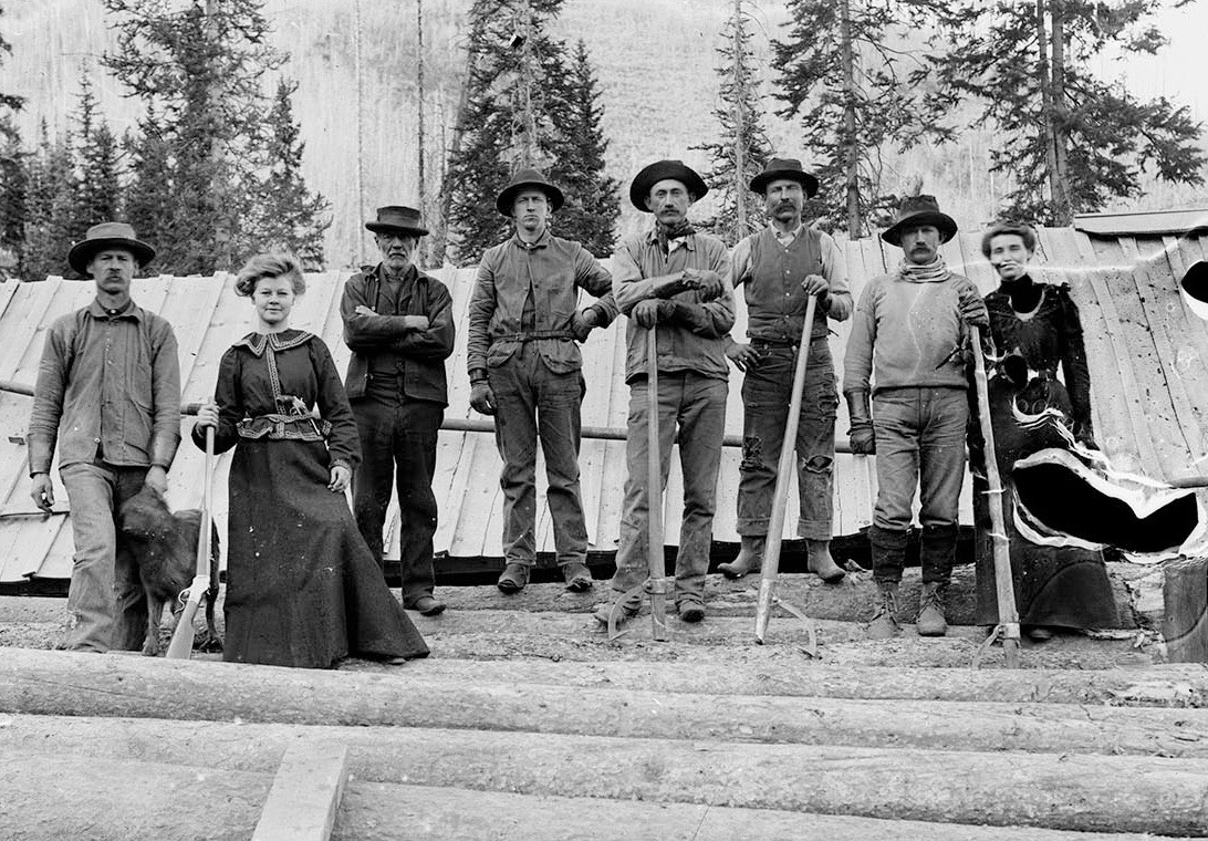 In 1900, a pistol-packing woman, second from left, holds a lever-action rifle (possibly a legendary Henry rifle) while standing with a group of sawyers and another woman of the era. They are holding peaveys, or 'cant dogs,' which were used to roll logs. Sawdust from the many local sawmills often went into the streams and river, disrupting the trout population. Photo credit: John Bowman via AHS, Shaw Collection.