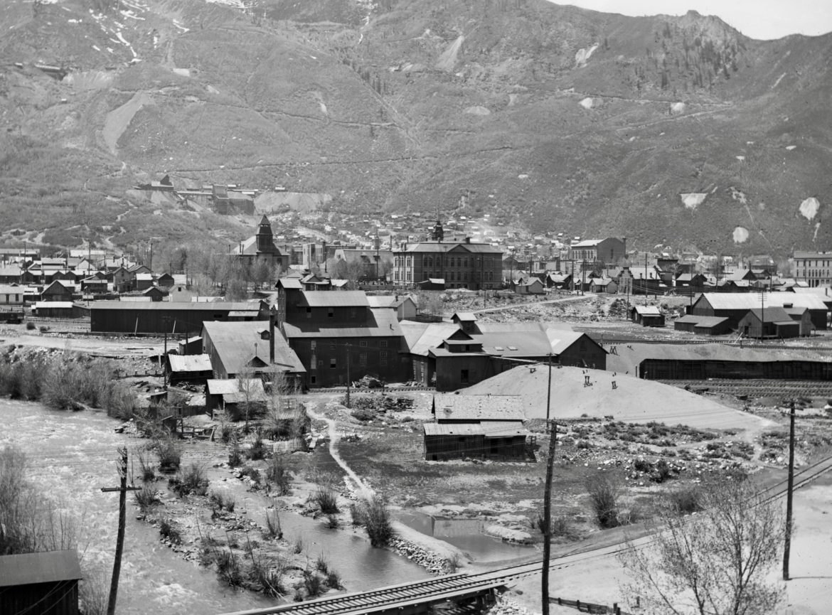 """This view of Aspen, in 1910, overlooks the Roaring Fork River and the Smuggler Concentrator plant, which processed zinc and lead. Its toxic tailings, along with untreated sewage from town, drained into the river. Note the two cabins between the concentrator and the river, each with an outhouse on the river. Just upriver from the mill, the Galena Street sewer outlet, across from """"Oklahoma Flats,"""" drains into the river. Photo credit: John Bowman via AHS, Shaw Collection"""