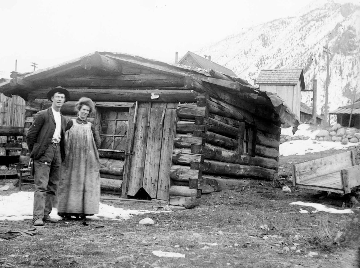 An Aspen couple, circa 1900, in front of their dirt-chinked cabin with a sod roof and opaque windows. The man holds what may be a miner's dinner pail behind his back and the woman's dress shows the stains of hard work. Behind the house is a barn and outhouse. East Aspen Mountain, home of today's Ute Trail, is visible, which suggests the cabin was in the Eames Addition, near the top of South Aspen Street. Photo credit: AHS, Masterson Estate Collection.