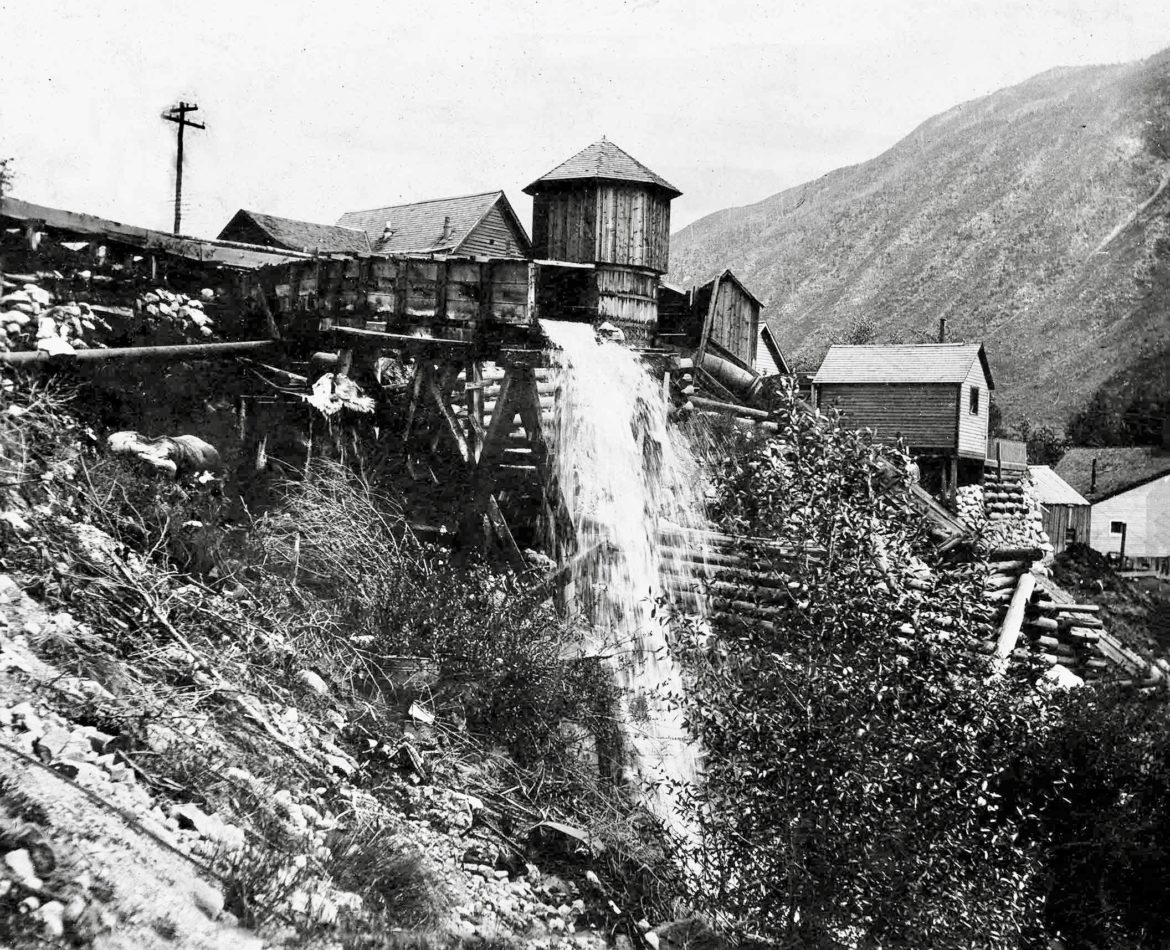 A flume carrying water discharge, and possibly mining discharge, flows into the Roaring Fork River, just above and east of the Neale Street Bridge (No Problem Bridge) in Aspen in 1910. On the right, a large-diameter pipe heads toward the river, too. The Ute Spring area is at the base of the mountain in the background. Photo credit: AHS, Masterson Estate Collection.