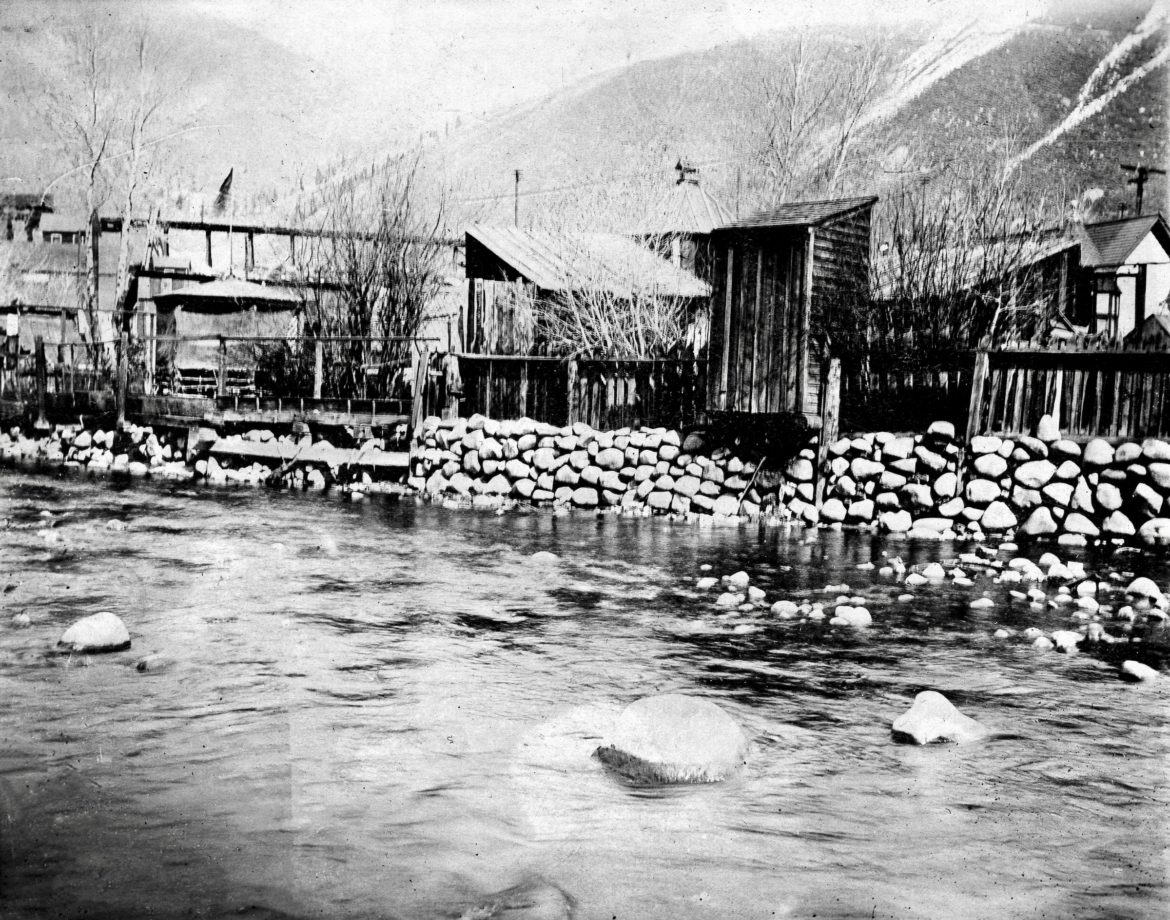 A convenient privy cantilevers over the Roaring Fork River in Aspen's Oklahoma Flats, circa 1900. It was a poor neighborhood populated by miners' shacks, right across the river from the Galena Street sewer outlet, which drained raw sewage from downtown. Photo credit: Aspen Historical Society