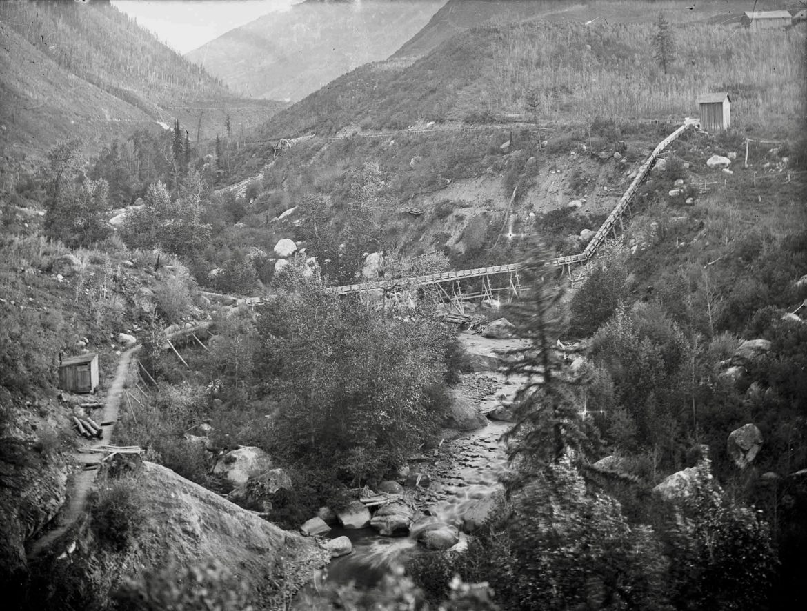 This photo shows the lower end of the Castle Creek ditch and flume water-delivery system to Aspen, part of Cowenhoven's and Brown's Aspen Water Company, which first piped water into west Aspen around the corner of Shadow Mountain and down West Hopkins Avenue. The photo was taken in 1900 near today's foot/bike path bridge over Castle Creek to the Holden/Marolt Mining and Ranching Museum. Photo credit: AHS, Shaw collection.